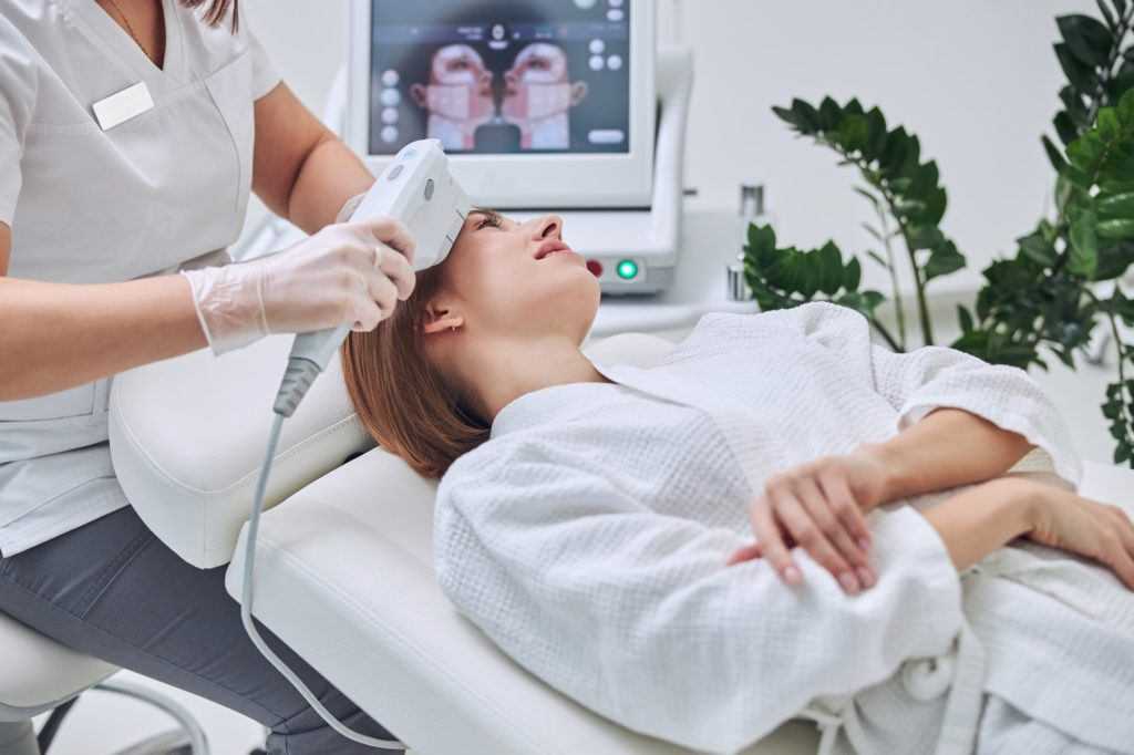 Beautiful Caucasian young female receiving professional skin care with special modern device in