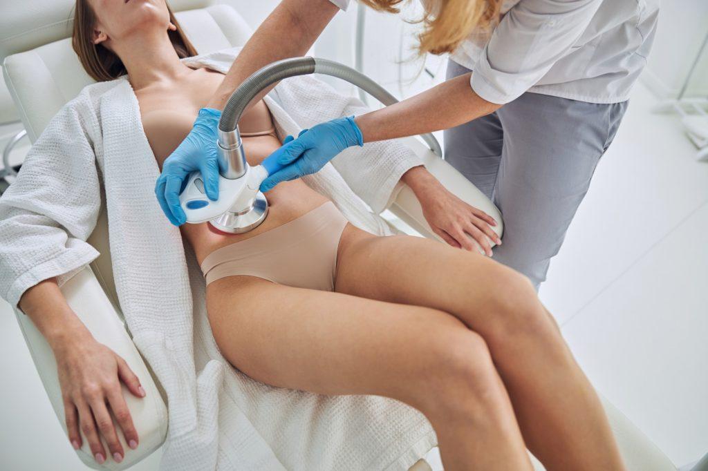 Unrecognized woman in white bathrobe receiving Ultrasound cavitation body contouring treatment in